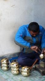 Un artisan décorant un bol tibétain